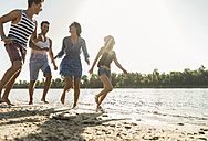 Happy friends running at the river - UUF005859