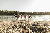 Friends with inner tubes running in river - UUF005874