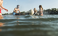 Happy friends with inner tubes and ball in water - UUF005883
