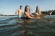 Happy friends with inner tube and ball in water - UUF005886