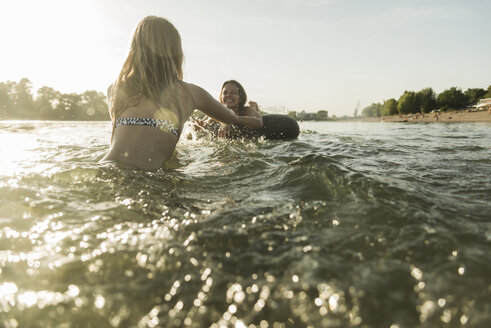 Two happy friends with inner tube in water - UUF005889