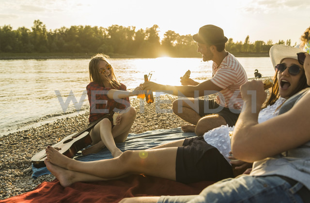 Friends relaxing at the riverside at sunset - UUF005901 - Uwe Umstätter/Westend61