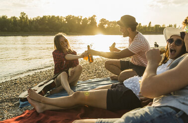 Friends relaxing at the riverside at sunset - UUF005901