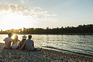 Friends relaxing at the riverside at sunset - UUF005916