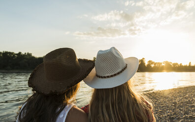 Two friends wearing straw hats relaxing at the riverside at sunset - UUF005919