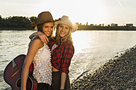 Two friends embracing at the riverside at sunset - UUF005922