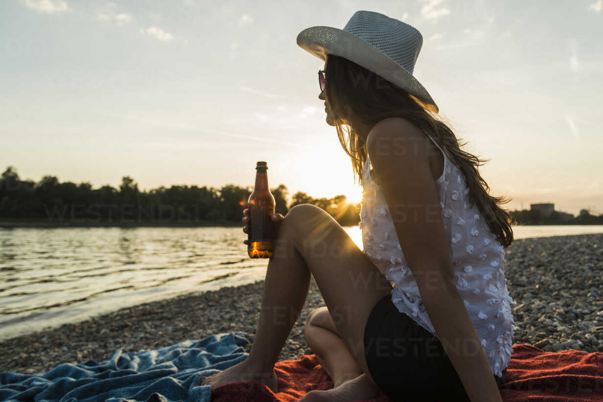 Young woman drinking beer at the riverside at sunset - UUF005928 - Uwe Umstätter/Westend61
