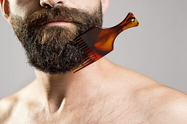 Bare-chested man with comb stuck in beard - JASF000183