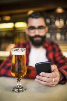 Bearded man sitting in bar, checking emails with beer on counter - JASF000192