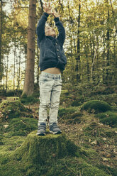 Little boy standing on tree stump reaching up - MFF002415