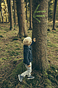 Little boy in forest touching bark of spruce tree - MFF002433
