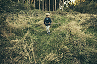 Little boy exploring forest, walking in grass with his stick - MFF002439