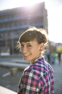 Germany, Berlin, portrait of smiling young woman at twilight - FKF001418