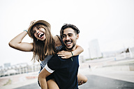 Spain, Barcelona, young man giving his girlfriend a piggyback ride - JRFF000142