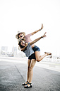 Spain, Barcelona, young woman giving her friend a piggyback ride - JRFF000145