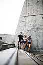 Spain, Barcelona, three friends leaning against concrete wall - JRFF000148