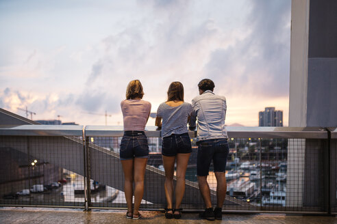 Spain, Barcelona, back view of three friends looking at view from a bridge - JRFF000151
