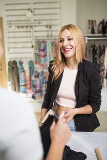 Young woman in fashion boutique paying for purchase - JASF000211