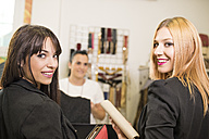 Young women in fashion boutique shopping for clothes - JASF000214