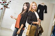 Young women in fashion boutique carrying shopping bags - JASF000229