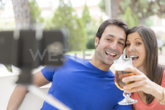 Happy couple using selfie stick for taking a selfie with smartphone - ERLF000063 - Enrique Ramos/Westend61