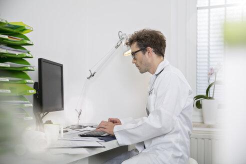 Doctor sitting at desk working on computer - FKF001441
