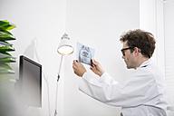 Dentist examining x-ray image - FKF001444