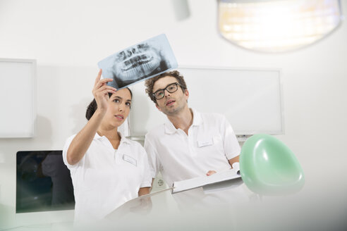 Two dentists in dental surgery discussing x-ray image - FKF001456