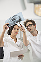 Two dentists in dental surgery discussing x-ray image - FKF001459