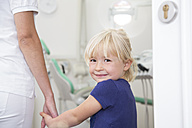 Dental assistant holding girl's hand before treatment - FKF001465
