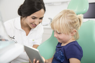 Dentist and smiling girl with digital tablet in dentist's chair - FKF001474