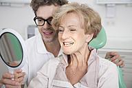 Senior woman in dentist's chair checking her teeth in mirror - FKF001483