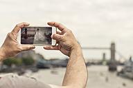UK, London, man taking photo of Tower Bridge with his smartphone - ZMF000434