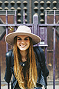 Spain, Barcelona, smiling young woman in front of entrance portal - EBSF000936