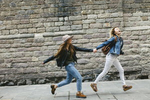 Spain, Barcelona, two young women running hand in hand in the city - EBSF000939