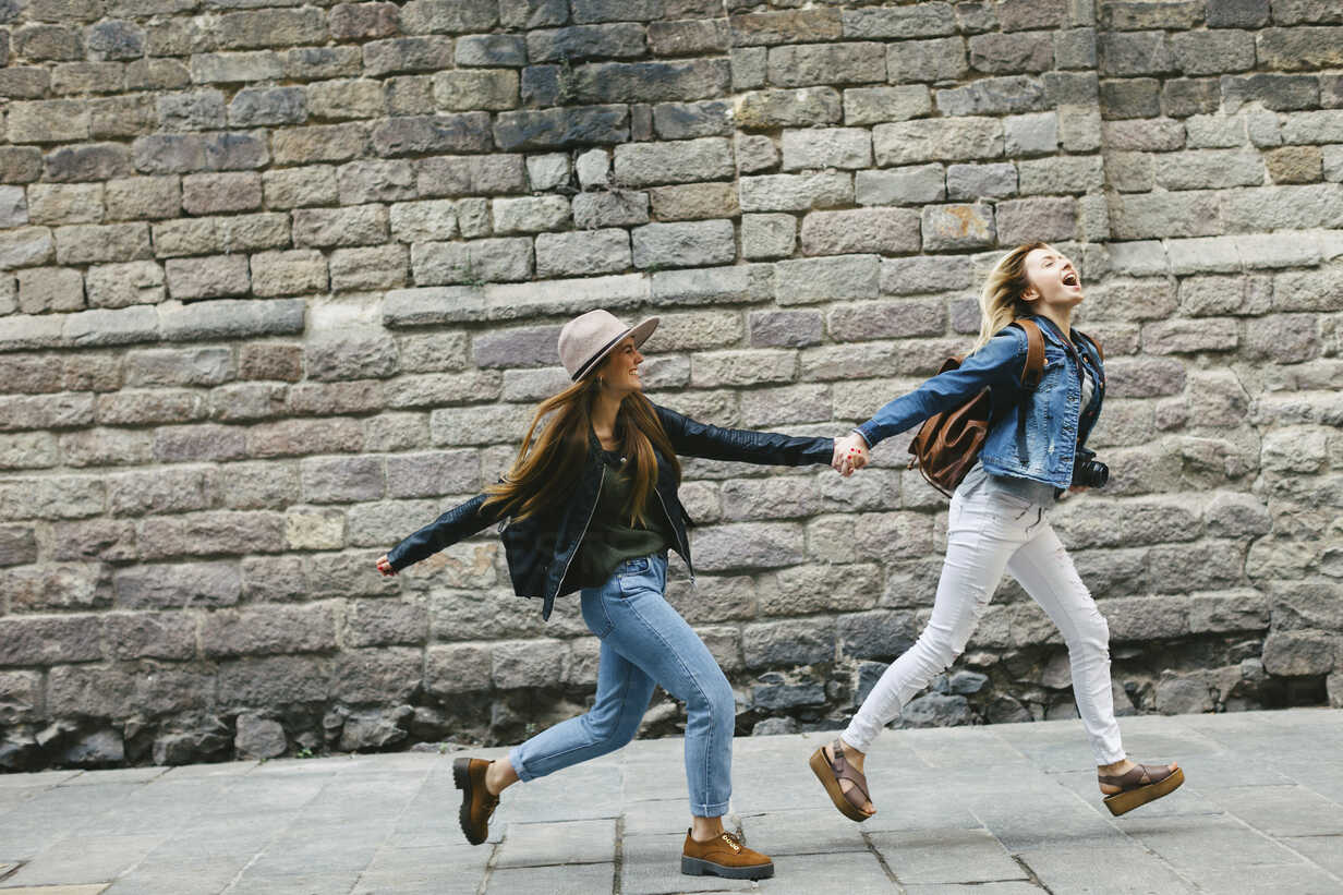Spain, Barcelona, two young women running hand in hand in the city - EBSF000939 - Bonninstudio/Westend61