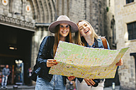 Spain, Barcelona, two happy young women reading map - EBS000942