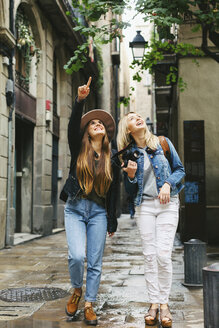 Spain, Barcelona, two young women walking in the city looking up - EBSF000945