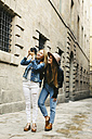 Spain, Barcelona, two young women walking in the city taking photos - EBSF000948