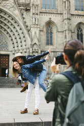 Spain, Barcelona, woman taking picture of two playful young women in the city in the city - EBSF000954