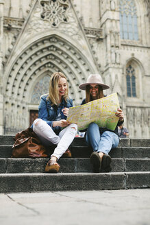 Spain, Barcelona, two happy young women reading map on stairs - EBS000957