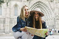 Spain, Barcelona, two happy young women reading map - EBS000960