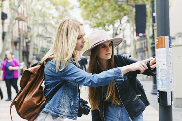 Spain, Barcelona, two young women looking at city map on pole - EBSF000966