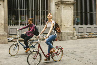Spain, Barcelona, two young women riding bicycle in the city - EBSF000969