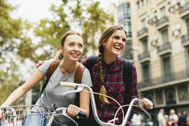 Spain, Barcelona, two young women on bicycles in the city - EBSF000972
