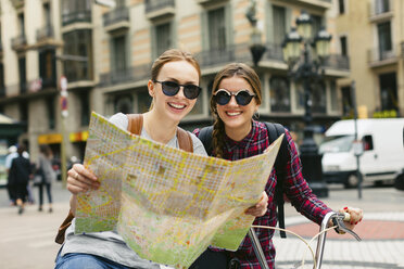 Spain, Barcelona, two happy young women with map on bicycles in the city - EBS000975