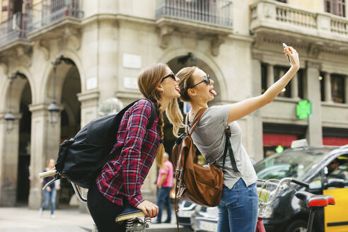 Spain, Barcelona, two playful young women taking a selfie - EBSF000978