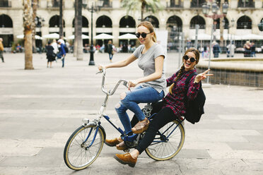 Spain, Barcelona, two happy young women sharing bicycle in the city - EBSF000981