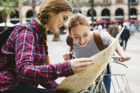 Spain, Barcelona, two young women with map on bicycles in the city - EBSF000984