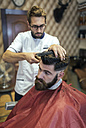 Barber cutting hair of a customer - MGOF000892